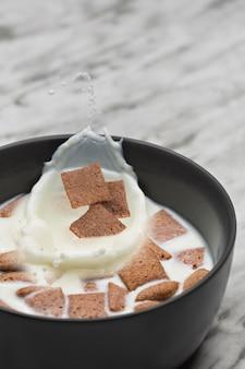 Hazelnootgraangewas in een kom met melkplons.