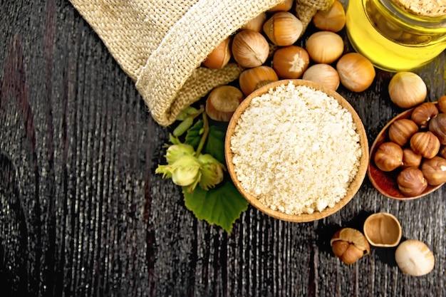 Hazelnootmeel in een kom, noten in zak, een lepel, olie in glazen pot en hazelnoottak met groene bladeren op houten plankachtergrond van bovenaf
