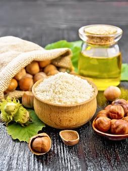 Hazelnootmeel in een kom, noten in zak, een lepel, olie in glazen pot en hazelnoottak met groene bladeren op zwarte houten plankachtergrond