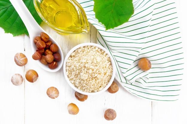 Hazelnootmeel in een kom, olie in een glazen juskom, noten, servet en hazelnoottak met groene bladeren op houten plankachtergrond van bovenaf