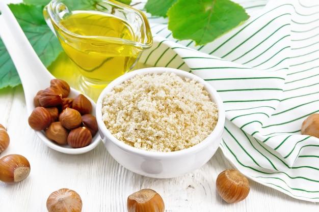 Hazelnootmeel in een kom, olie in een glazen juskom, noten, servet en hazelnoottak