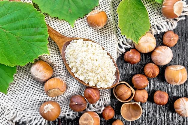 Hazelnootmeel in een lepel en noten op plundering, hazelnoottak met groene bladeren op houten plankachtergrond van bovenaf