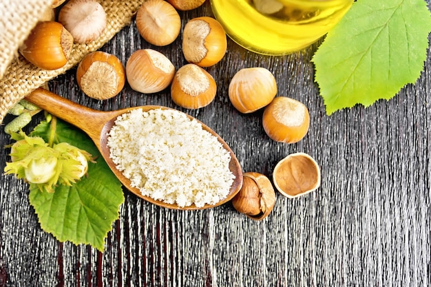 Hazelnootmeel in een lepel, noten in een zak en op tafel, olie in glazen pot en hazelnoottak met groene bladeren op houten plankachtergrond van bovenaf