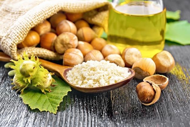 Hazelnootmeel in een lepel, noten in een zak en op tafel, olie in glazen pot en hazelnoottak met groene bladeren op houten plankachtergrond