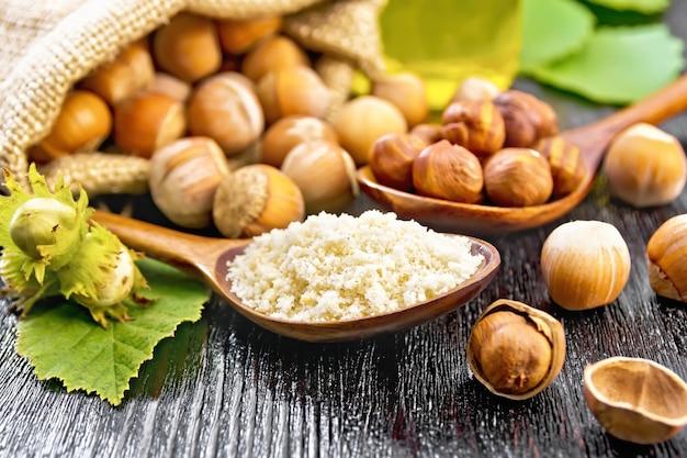 Hazelnootmeel in een lepel, noten in een zak, lepel en op tafel, olie in glazen pot en hazelnoottak met groene bladeren op donkere houten plankachtergrond