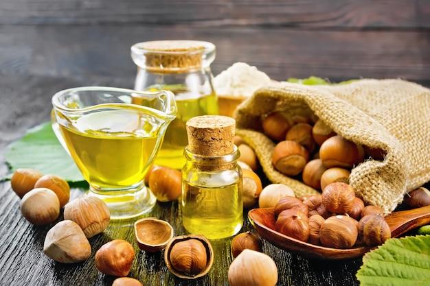 Hazelnootolie in een glazen fles, pot en juskom, bloem in een kom, noten in zak, lepel en op tafel, hazelnoottakjes met groene bladeren op houten plankachtergrond