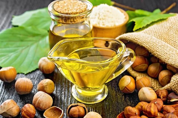 Hazelnootolie in een glazen pot en juskom, bloem in een kom, noten in een zak, lepel en op tafel, hazelnoottakjes met groene bladeren op houten plankachtergrond