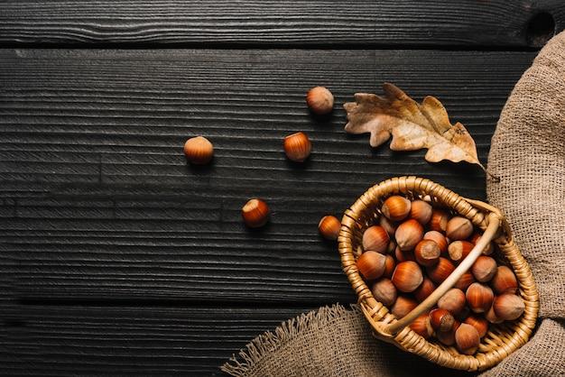 Hazelnoten en gedroogd blad dichtbij doek
