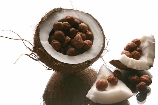 Hazelnoten in een gespleten kokosnoot op witte achtergrond