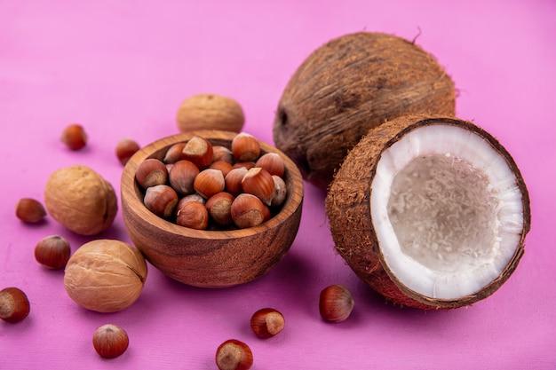 Hazelnoten op een houten kom met verse kokosnoten en walnoten geïsoleerd op roze oppervlak