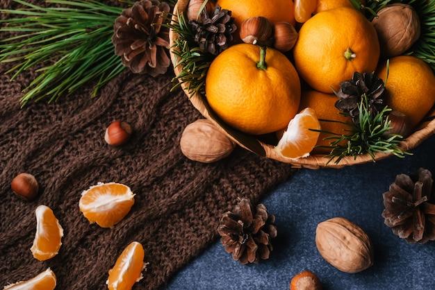 Hazelnoten, walnoten en mandarijnen versierd met kersttakken en dennenappels