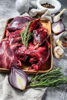 Hazenvlees. rauwe verse wilde haas op een houten tafel met groenten en kruiden. bovenaanzicht. biologisch vlees