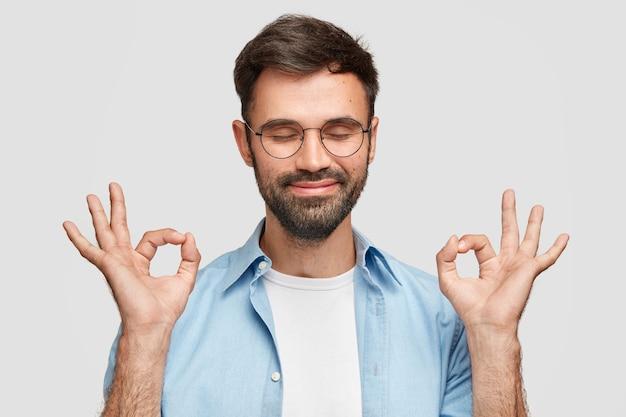 Hé, ik heb iets! tevreden tevreden man met dikke baard, zegt dat alles in orde is en met gebaren onder controle is