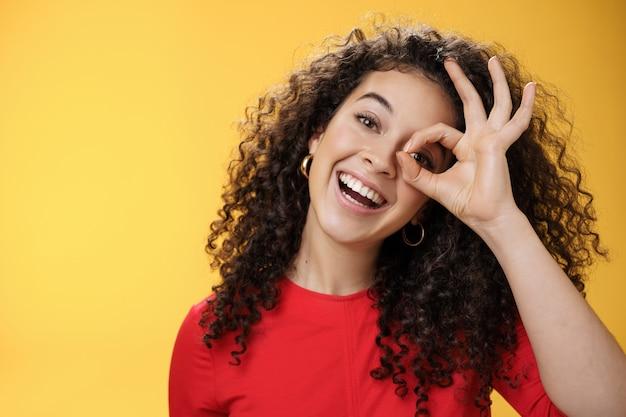 Hé, ik zie je. charismatische grappige en speelse schattige tedere vriendin met krullend haar die een goed of nulgebaar toont boven de ogen die naar de camera gluren en breed glimlachen, het hoofd schuin over de gele muur.