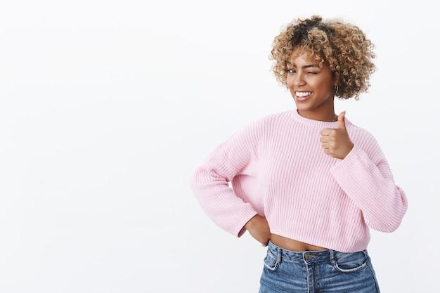 Hé, jij bent de beste. portret van flirterige en gelukkige charismatische afro-amerikaanse vrouw met blond kapsel die vrolijk knipoogt en glimlacht als duim omhoog in like en goedkeuringsgebaar over witte muur