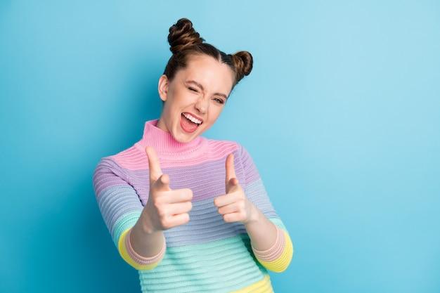 He jij. foto van aantrekkelijke gekke funky dame twee broodjes die vingers op camera richten knipperend oog flirterig persoon kies uitgezocht draag casual warme gestreepte trui geïsoleerde blauwe kleur achtergrond