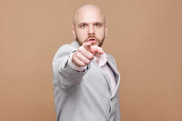 He jij! portret van een serieuze, knappe, kale, bebaarde, bazige zakenman van middelbare leeftijd in een klassiek grijs pak die staat en met de vinger naar de camera wijst. indoor studio opname, geïsoleerd op lichtbruine achtergrond.