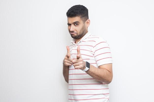 He jij. portret van een tevreden knappe bebaarde jongeman in een gestreept t-shirt die staat, kijkt en wijst naar de camera met een grappig gezicht. indoor studio opname, geïsoleerd op een witte achtergrond.
