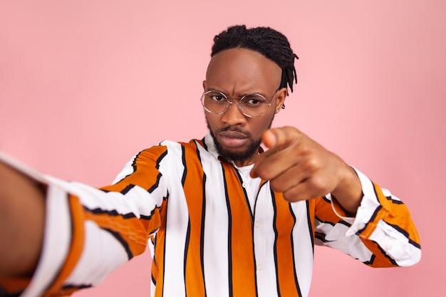 He jij! strikte onbeschofte afro-amerikaanse man blogger die met de vinger naar je wijst en serieus naar de camera kijkt