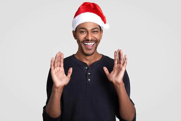 Hé, jongens, de kerstman komt naar je toe! blij donkerhuidig positief mannetje met brede glimlach, steekt handen op en toont handpalmen, draagt feestmuts, modellen op wit. vakantie en emoties.