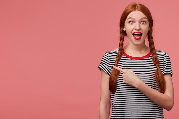 Hé, kijk, het is geweldig! gelukkig geïnspireerde roodharige tienermeisje toont met wijsvinger op de lege ruimte aan de linkerkant, is opgetogen over het product, adviseert op te letten, plaats voor uw advertentie