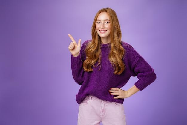 Hé, klik hier. portret van vriendelijk ogende charmante en schattige roodharige vrouw in paarse trui wijzend naar de linkerbovenhoek met wijsvinger en glimlachen, kopieerruimte tonen, aanbevelen, aanbieden.