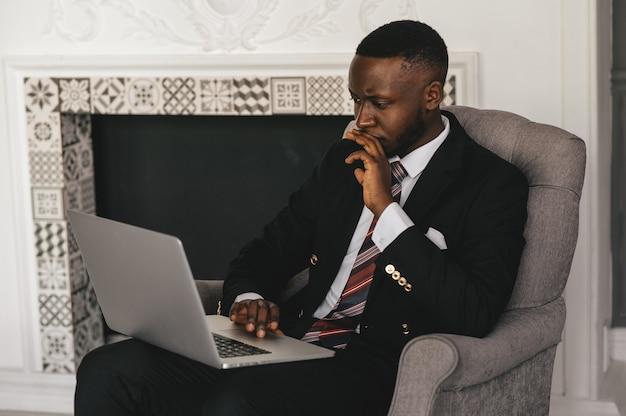 Head shot ernstige verbaasd afro-amerikaanse zakenman laptop scherm kijken