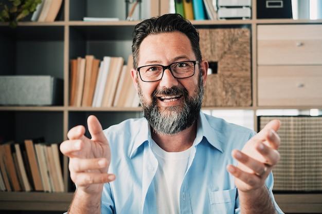 Head shot portret zelfverzekerde zakenman coach met een bril die naar de camera kijkt en praat, mentorspreker die online les houdt, uitlegt, zit aan een houten bureau in een moderne kast