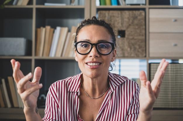 Head shot portret zelfverzekerde zakenvrouw coach met een bril die naar de camera kijkt en praat, mentorspreker die online les houdt, uitlegt, zit aan een houten bureau in een moderne kast
