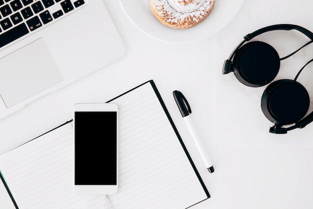 Headphone; laptop; mobiele telefoon; dagboek; pen en gebakken voedsel op witte achtergrond