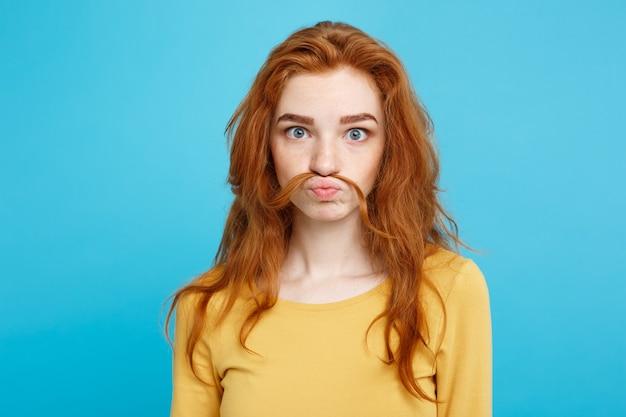 Headshot portret van gelukkig gember rood haar meisje imiteren om een man te zijn met haar nep snor pastel blauwe muur kopie ruimte