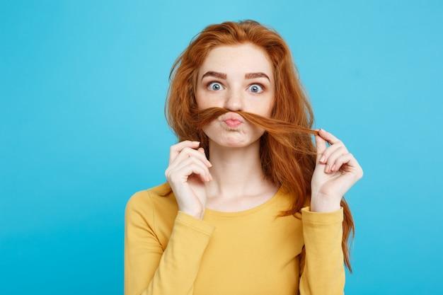 Headshot portret van gelukkig gember rood haar meisje imiteren om man met haar nep snor. pastel blauwe achtergrond. copy space.
