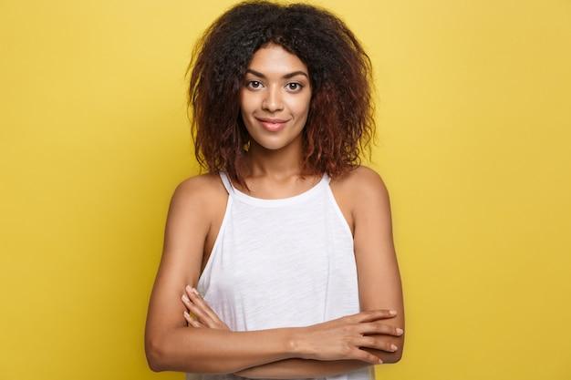 Headshot portret van mooie aantrekkelijke afrikaanse amerikaanse vrouw posten gekruiste armen met blij lachend. gele studio achtergrond. ruimte kopiëren.