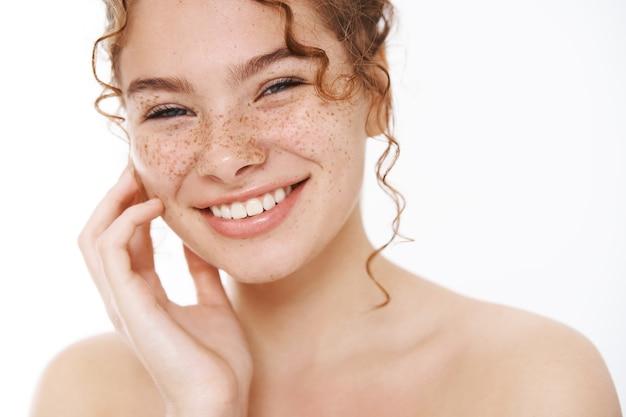Headshot tevreden tedere glimlachende roodharige schattig meisje sproeten krullend haar, staande naakte witte achtergrond lachend gelukkig zachtjes aanraken wang zorg voor huid als resultaat cosmetologie product aanbrengen