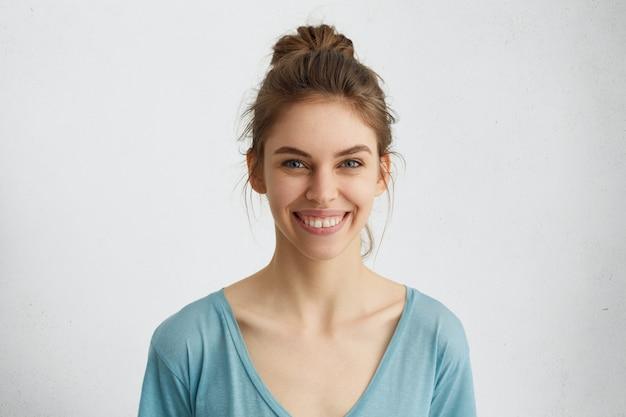 Headshot van aangenaam ogende jonge blanke vrouw met brede glimlach die haar rechte witte tanden toont die gelukkig zijn