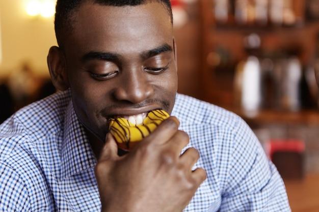 Headshot van aantrekkelijke jonge afro-amerikaanse zakenman donut bijten