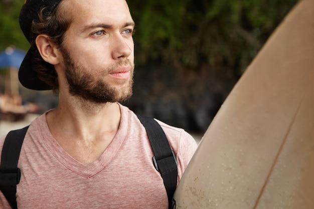 Headshot van aantrekkelijke jonge blanke man met weemoedige gezichtsuitdrukking houden paddle board