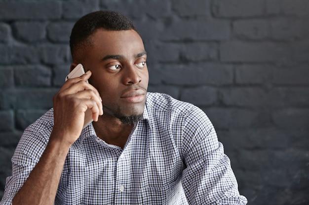 Headshot van aantrekkelijke jonge kantoormedewerker in formele slijtage met serieus telefoongesprek met zijn baas