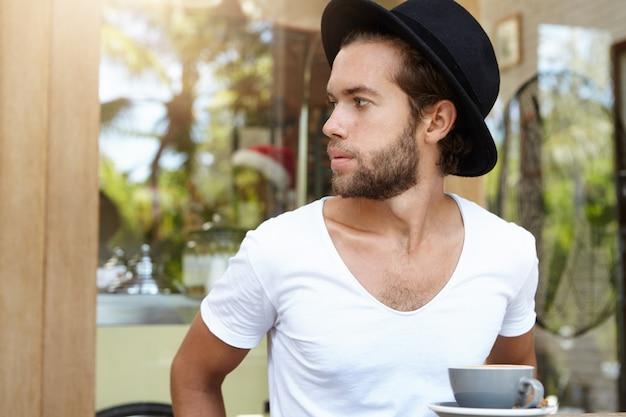 Headshot van aantrekkelijke jonge man met stijlvolle baard zitten in cafe, wegkijken, proberen te zien van ober