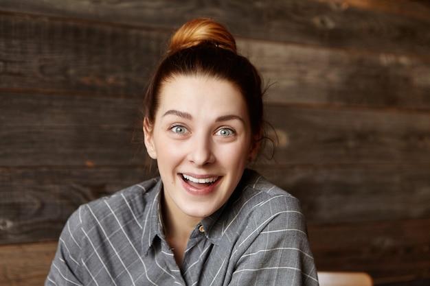 Headshot van aantrekkelijke jonge roodharige vrouw met haar broodje zit in café, gelaatsuitdrukking hebben verrast