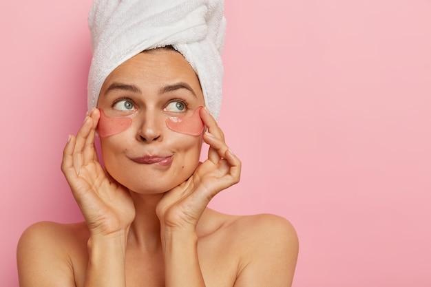 Headshot van aantrekkelijke jonge vrouw past hydrogelpleisters onder de ogen toe, bijt onderlip, verwijdert donkere kringen, kijkt opzij, staat naakt tegen roze muur. huidverzorging en beauty concept.