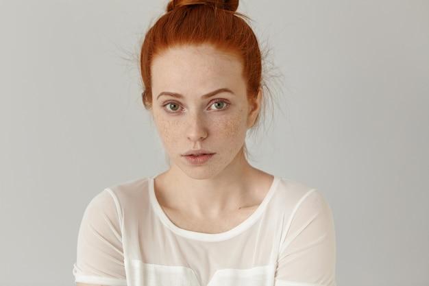 Headshot van aantrekkelijke jonge vrouw van buitengewone verschijning op zoek met verlegen subtiele glimlach gekleed in witte blouse.