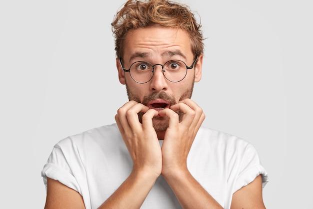 Headshot van aantrekkelijke man kijkt met verbaasde angstige nerveuze uitdrukking, heeft een probleem op het werk, bijt nagels, nonchalant gekleed, ontvangt slecht nieuws