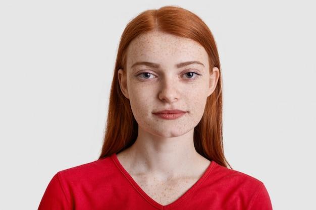 Headshot van aantrekkelijke roodharige europese vrouw met sproeten huid, serieus kijkt naar de camera, heeft minimale make-up, draagt rode trui, geïsoleerd op wit. natuurlijke schoonheid concept