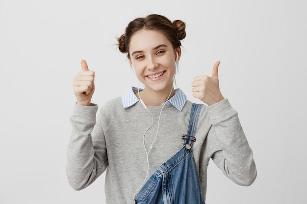 Headshot van aantrekkelijke vrouw die het toevallige positief stellen met omhoog duimen dragen. betaalbaar vrouwelijk model dat nieuwe oortjes adverteert in winkelgebaren als een teken.