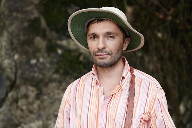 Headshot van aantrekkelijke wetenschapper met stoppels die buiten op rotsen staan tijdens het uitvoeren van wetenschappelijke studie bij veldwerk in natuurpark.