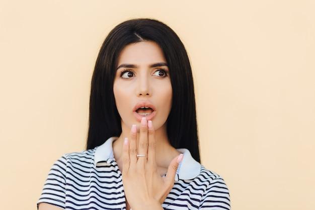 Headshot van bang brunette vrouw bedekt mond met hand, kijkt opzij met angst