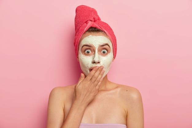 Headshot van bange vrouw staart met afgeluisterde ogen, bedekt de mond in omg-uitdrukking, handdoek op het hoofd gewikkeld, kleimasker op gezicht van toepassing, verbetert de huid