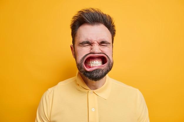 Headshot van bebaarde supergekke volwassen man klemt tanden op elkaar sluit ogen heeft wijd geopende mond draagt casual shirt