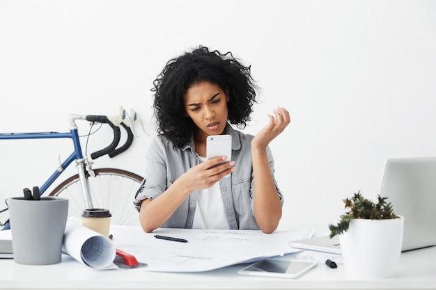 Headshot van bezorgde of gefrustreerde jonge architect die van de gemengd rasvrouw dringend sms-bericht leest